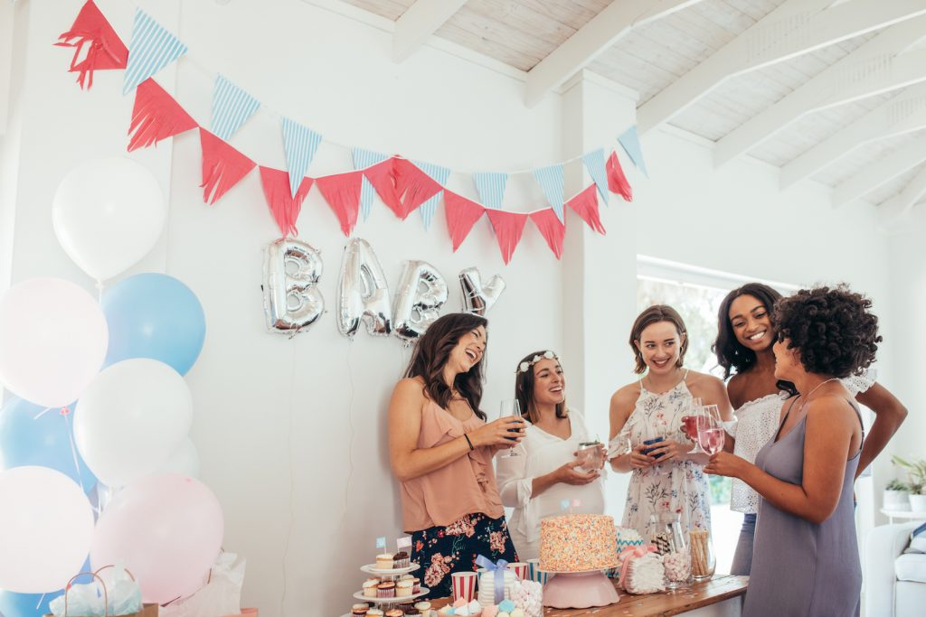 Pregnant woman celebrating baby shower with female friends at home.