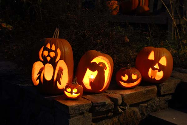 carved pumpkins lit up at night for halloween party decorations