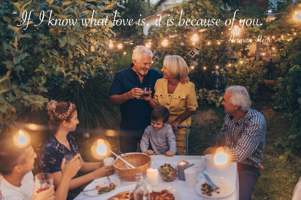 Photo of a senior couple, celebrating their anniversary with family, having a dinner outdoors in the back yard