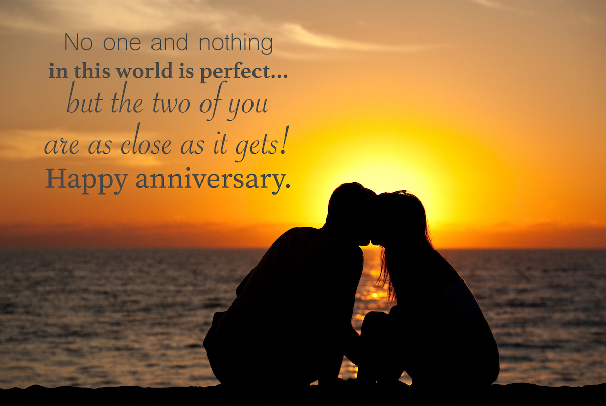 A romantic couple sitting on a beautiful beach kissing. Silhouette with anniversary wishes overlay.