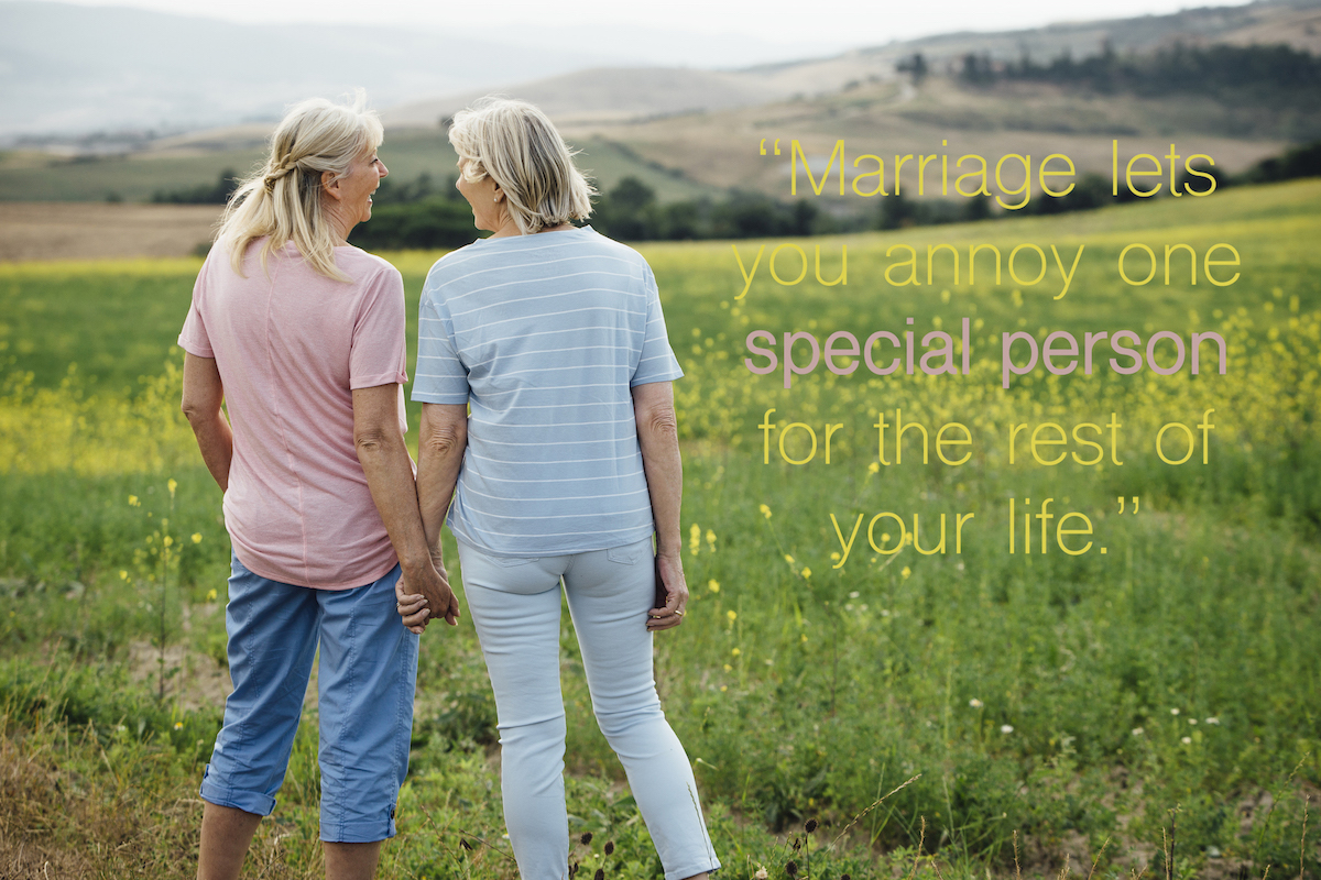 Two female women standing hand in hand as they smile at each other. Rear view of them both with the Italian countryside in front of them with a funny anniversary quotes for parents overlay