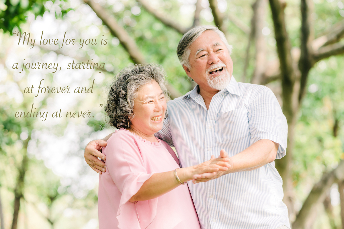 Happy senior Asian couple dancing in the park in sunny day with wedding anniversary quotes for parents overlay
