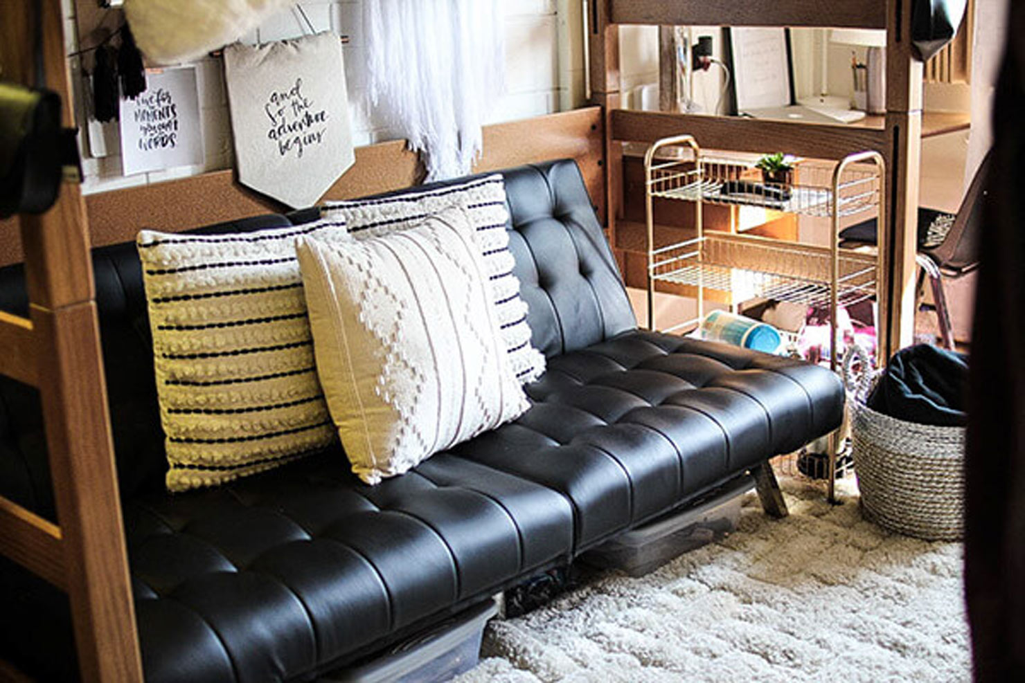 a bunk bed with a black couch below it.