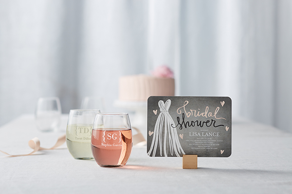 black and pink bridal shower invitation on counter next to wine glasses