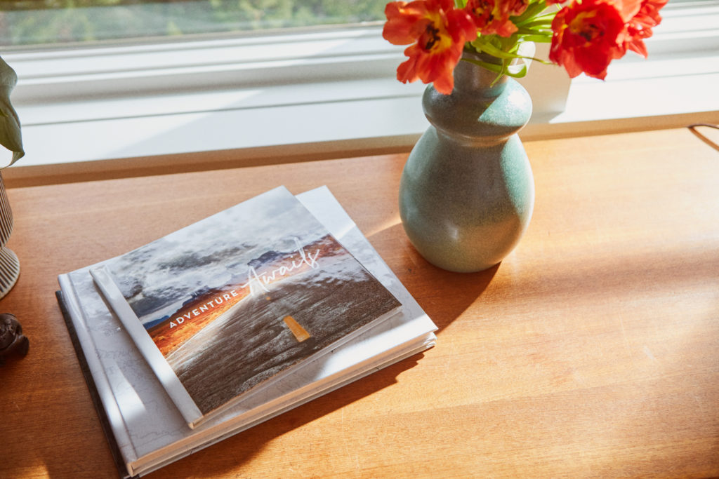 A custom photo book that says adventure awaits on a table next to a vase of flowers