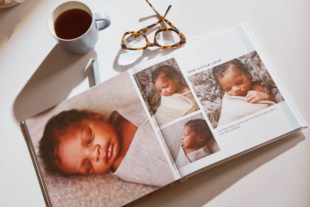 A baby photo book with a collage of baby photos next to glasses and a cup of coffee