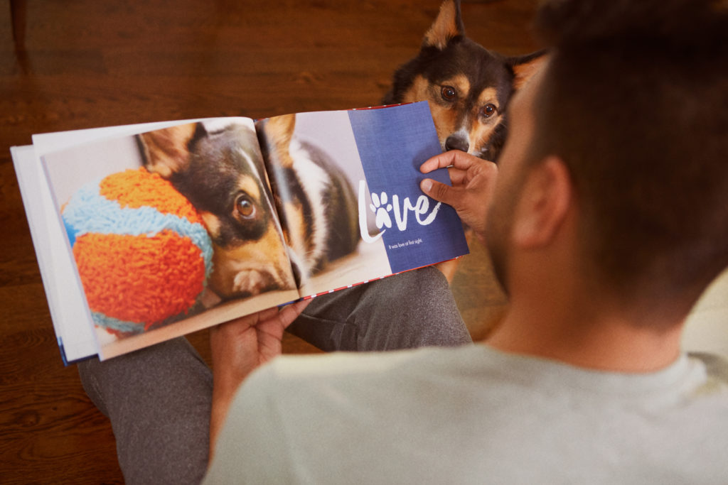 A man looking at a custom photo book made with photos of his dog