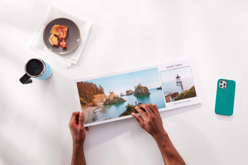 A person flipping through a photo book with images of a vacation