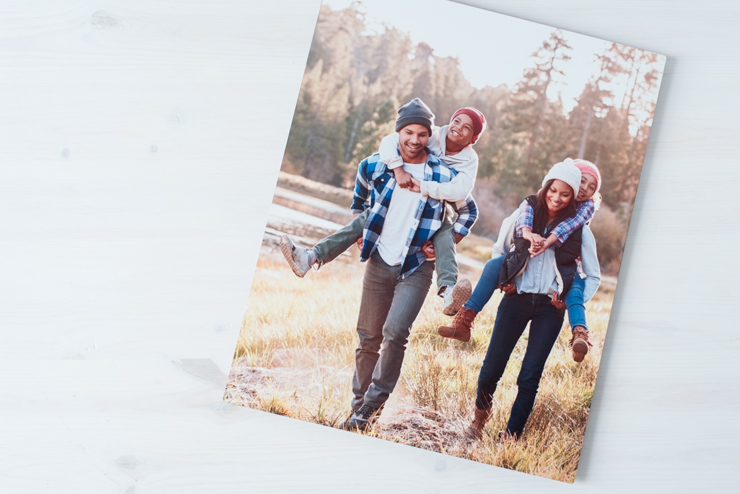 Family on metal art in outdoor gear with kids piggy backing on mom and dad