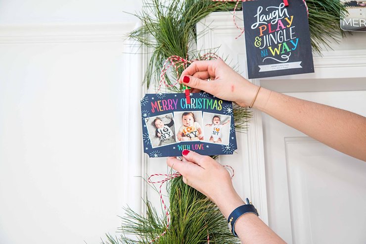clipping holiday cards onto christmas garland
