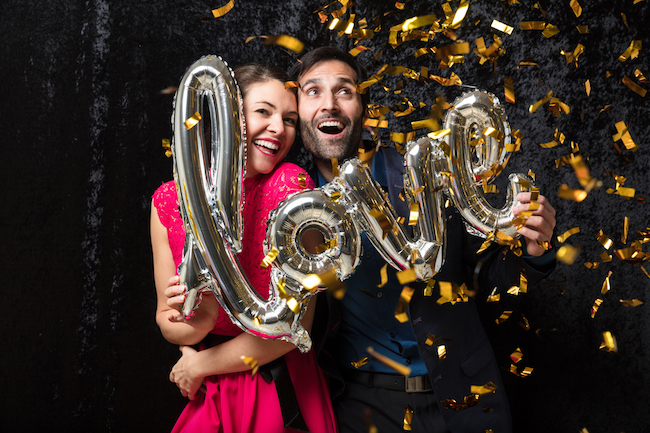 Cheerful couple celebrating with love balloon at an engagement party