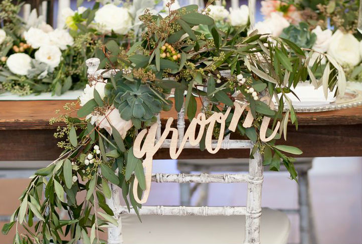 groom seat is decorated with greenery
