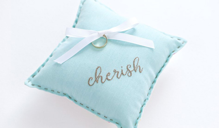 a blue pillow with a ring tied to it
