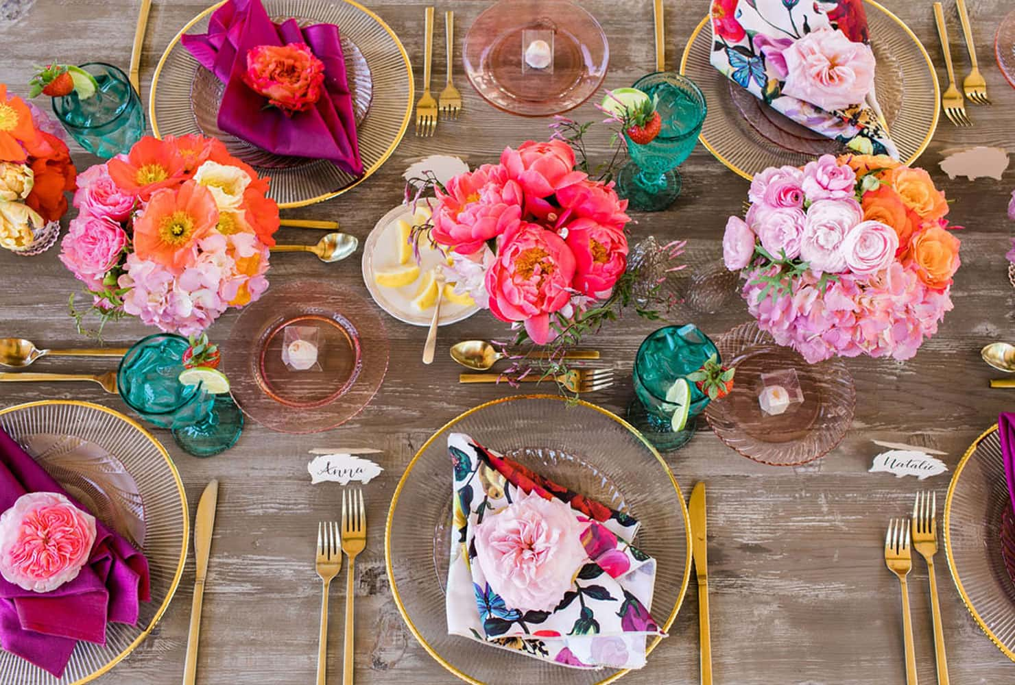 Wood table with bright florals and colorful napkins and drinkware