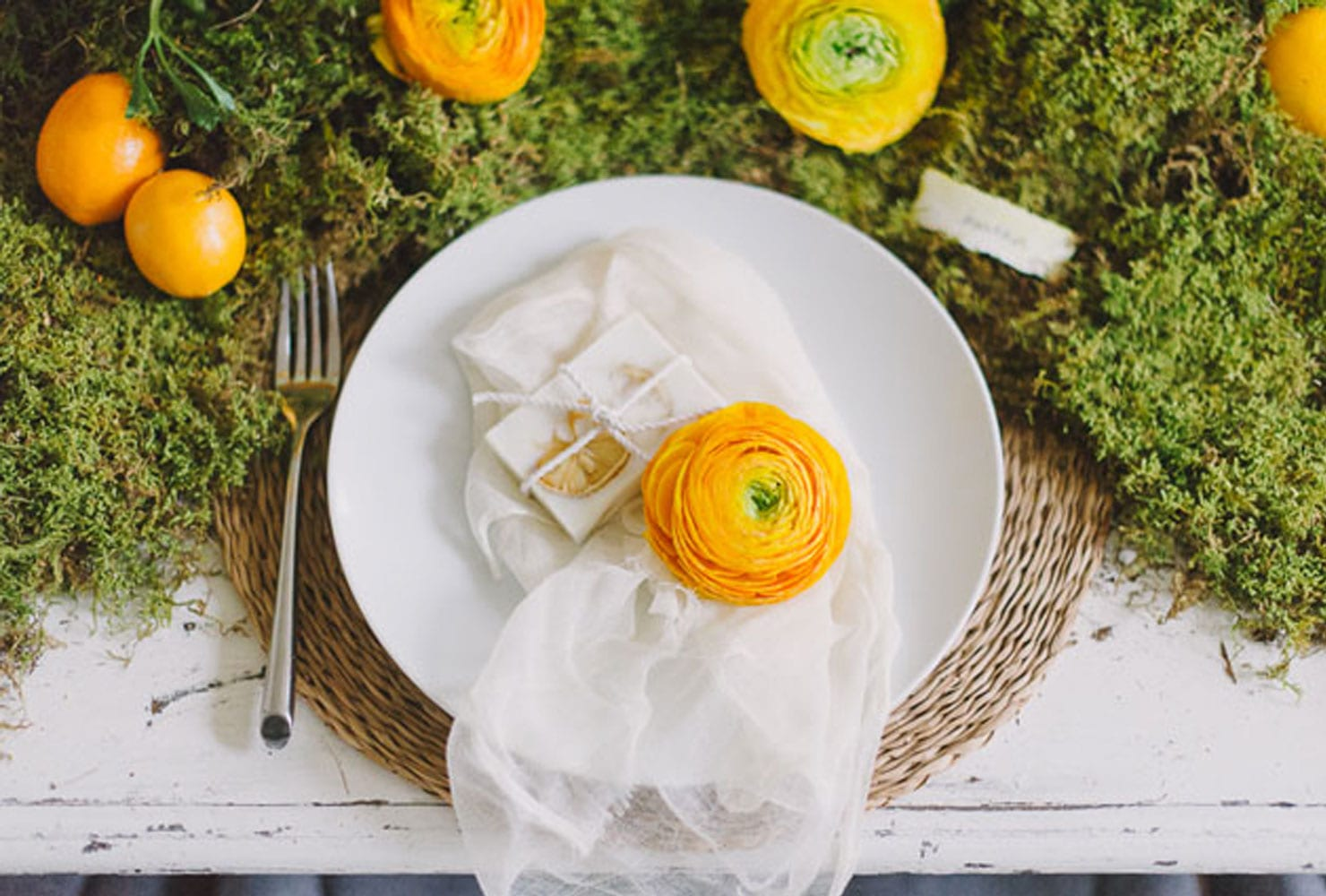 White table with moss and citrus fruits