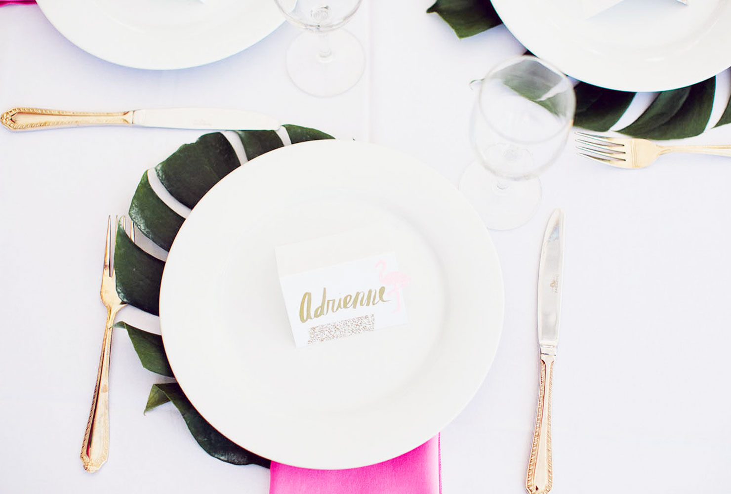 White plates on palm leaves with pink napkins and gold flatware