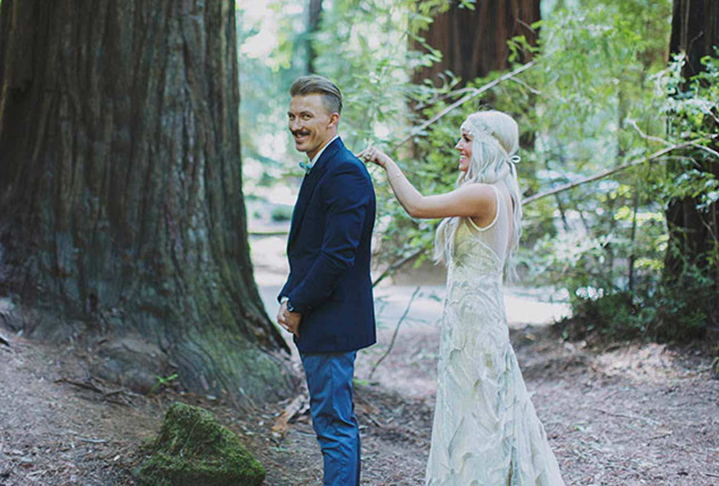 Groom looking at camera while bride taps him on the shoulder