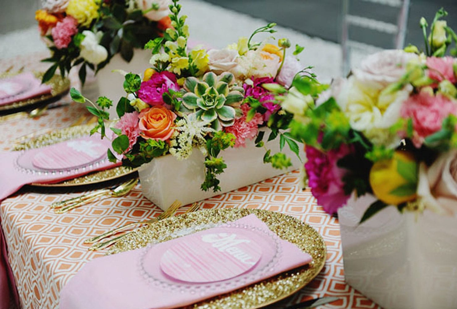 Bright floral centerpieces with light pink menus on gold glitter plates
