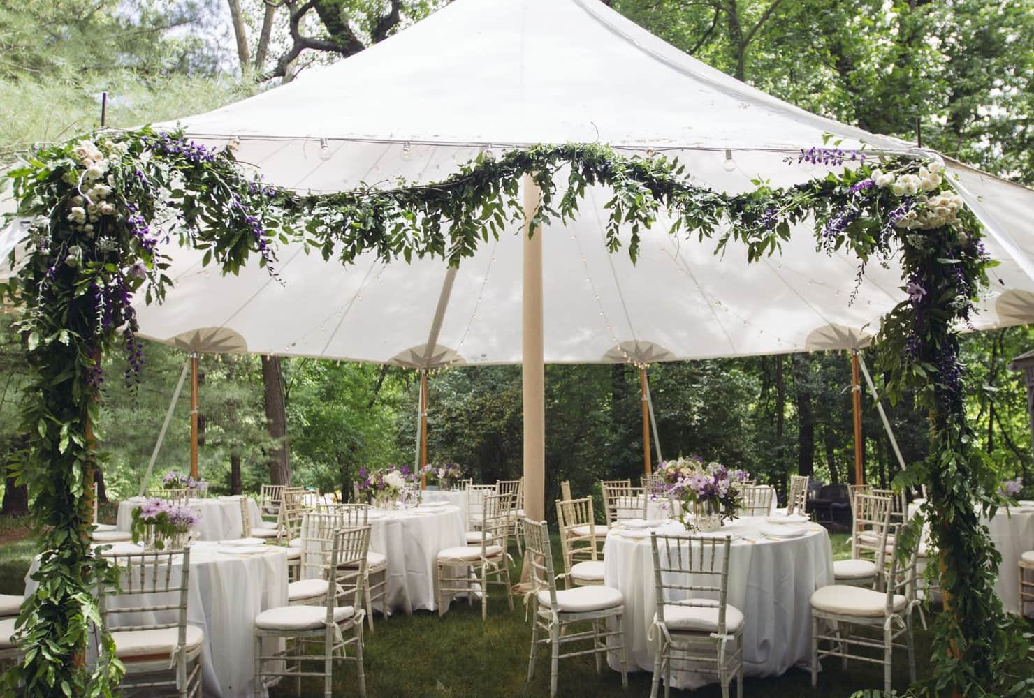 Garden party under white canopy and draping greenery