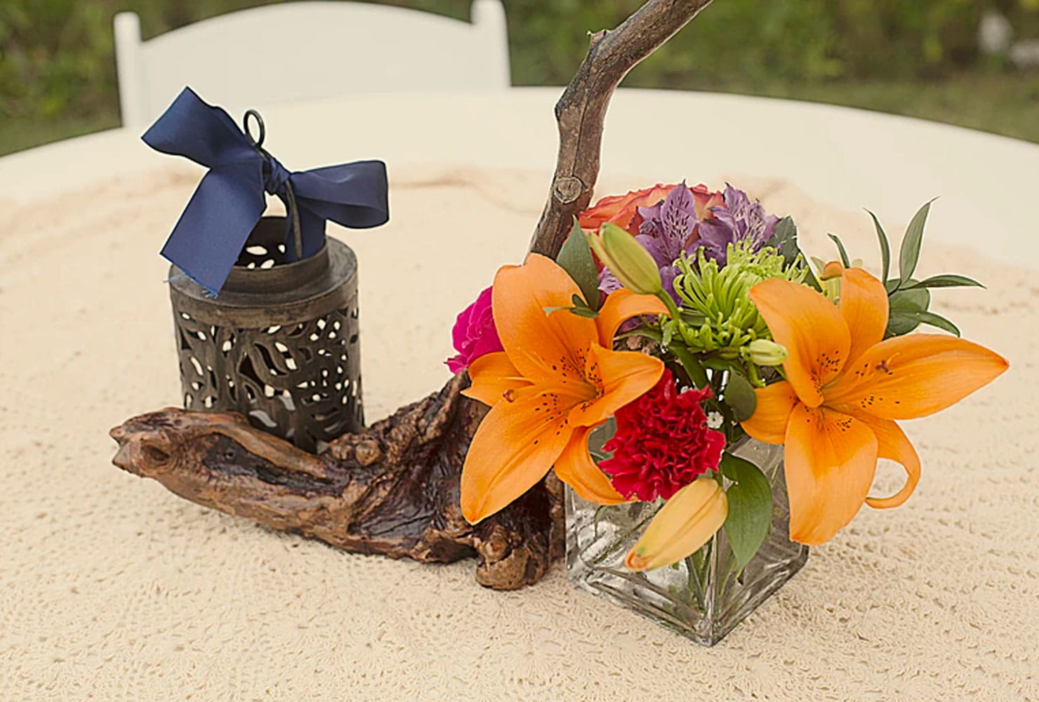 Driftwood centerpiece with bright florals and black candle votive