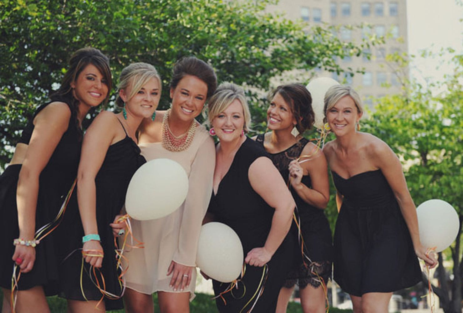 Bridal party in black and nude dresses with white balloons