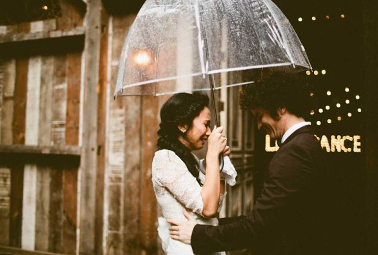Emotional bride holding clear umbrella with groom