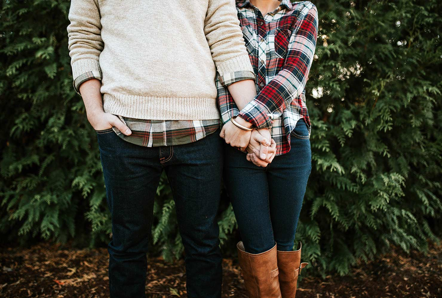 couple wearing plaid holding hands