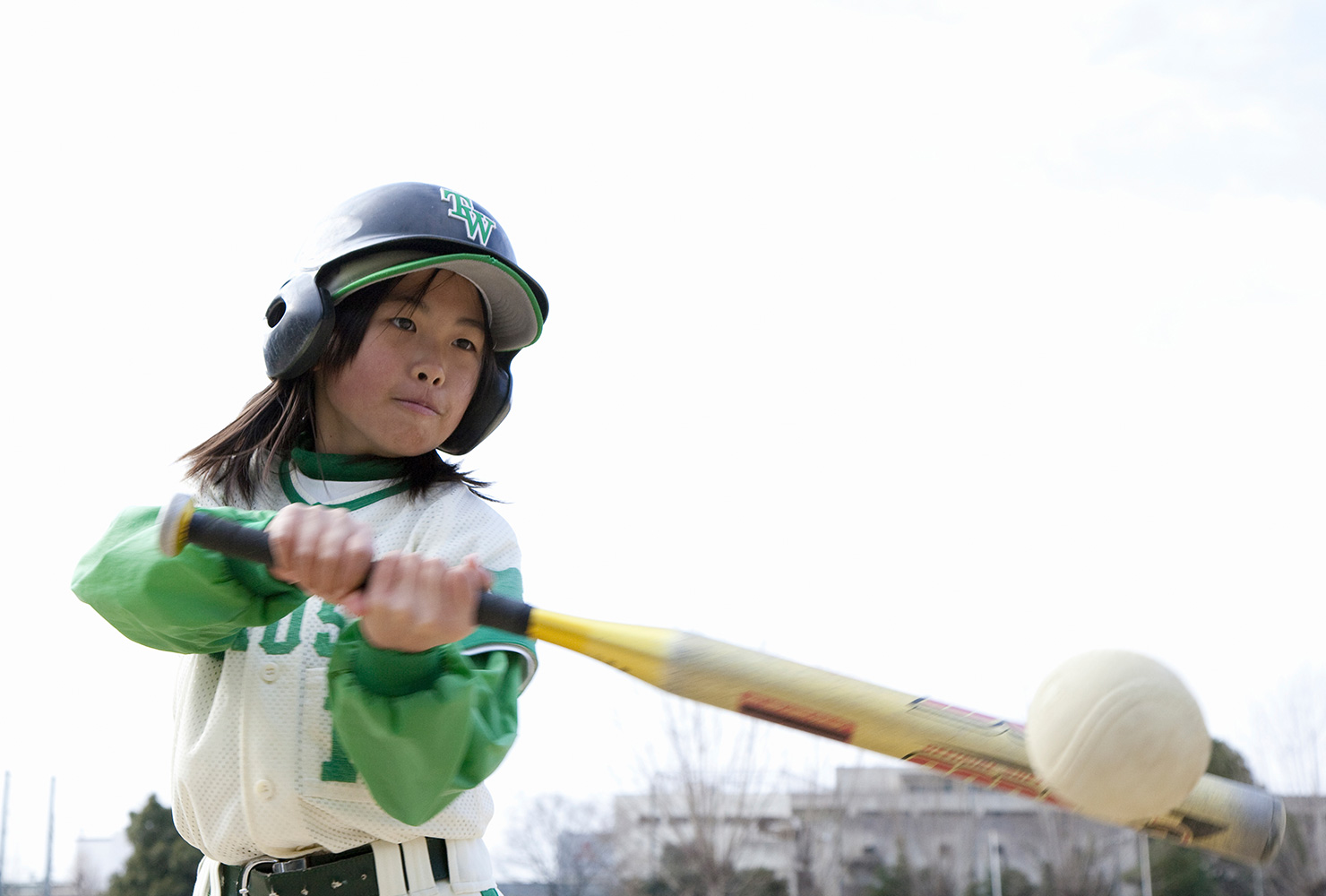 girl hitting a baseball