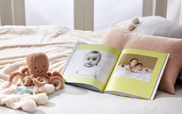 A baby photo book on a bed.