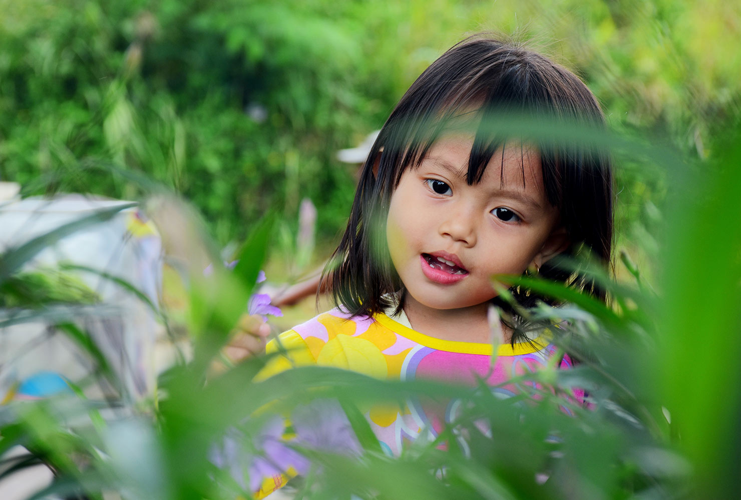little girl playing behind leaves