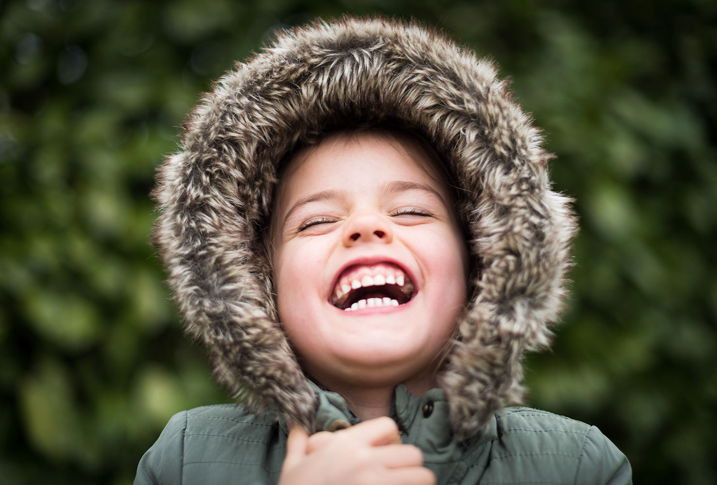 young child laughing wearing fuzzy jacket hood
