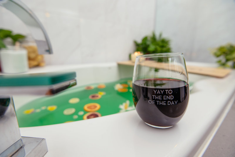 green wellness bath and a glass of wine