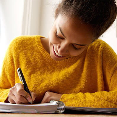 girl in a yellow sweater writing in a journal