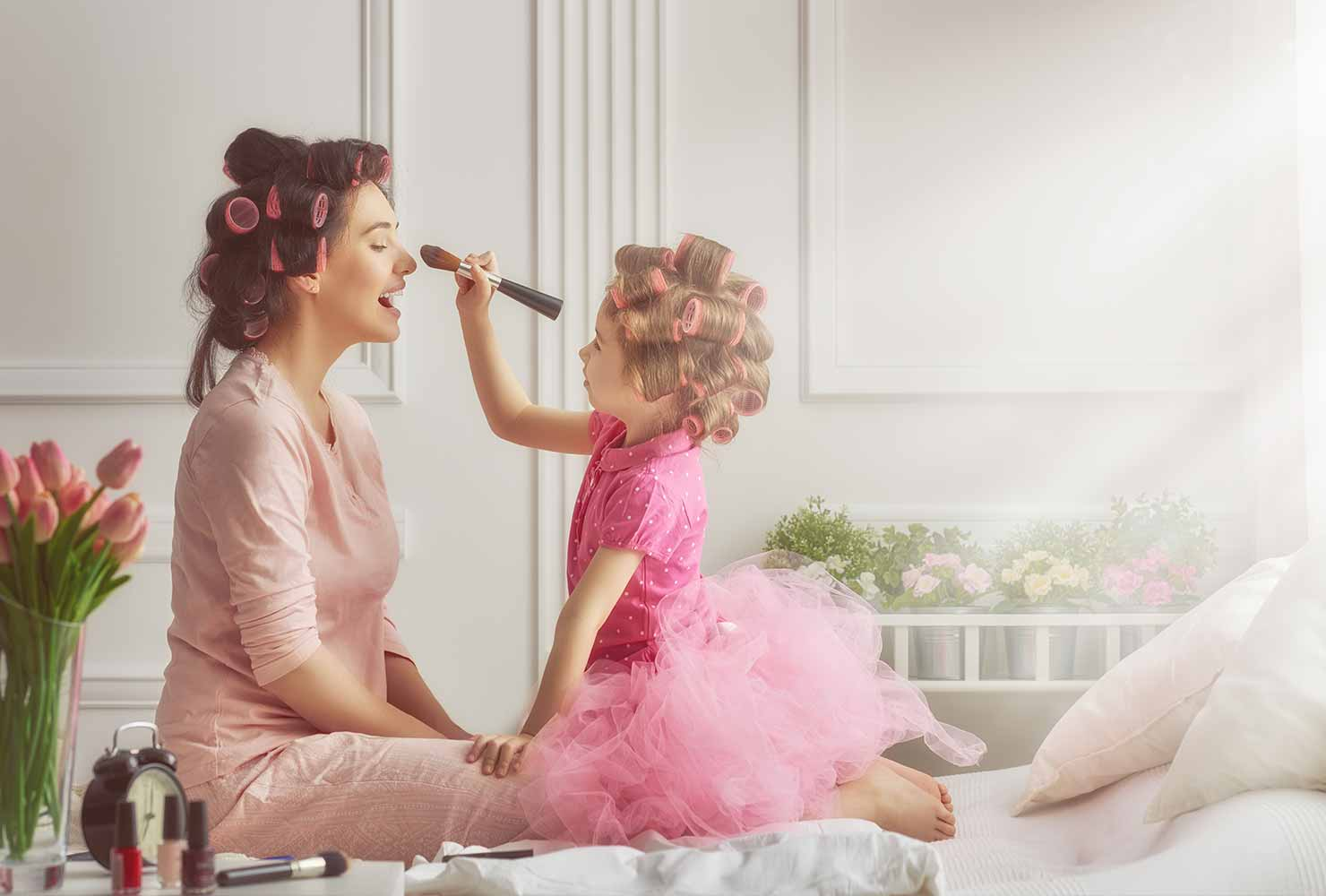 mom and daughter playing dress up and doing makeup
