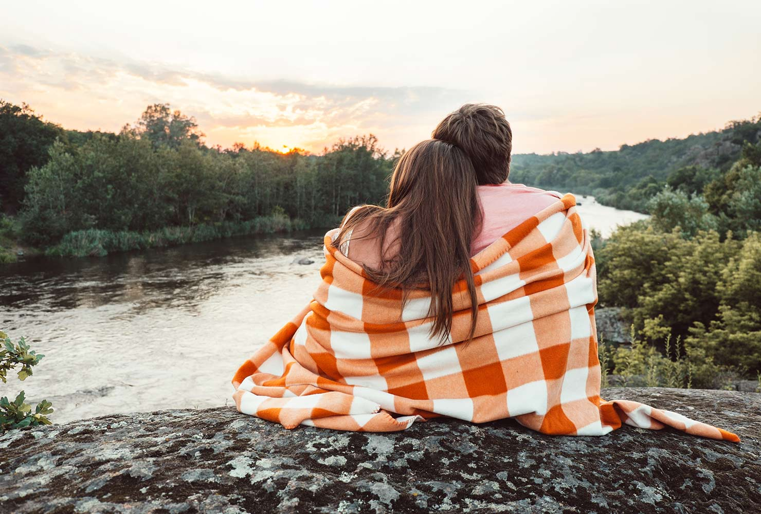 couple watching a sunset wrapped in a blanket