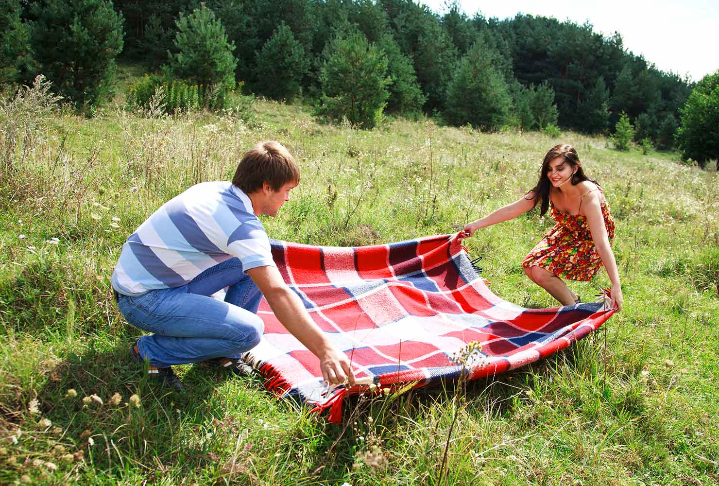 couple laying down a picnic blanket outside