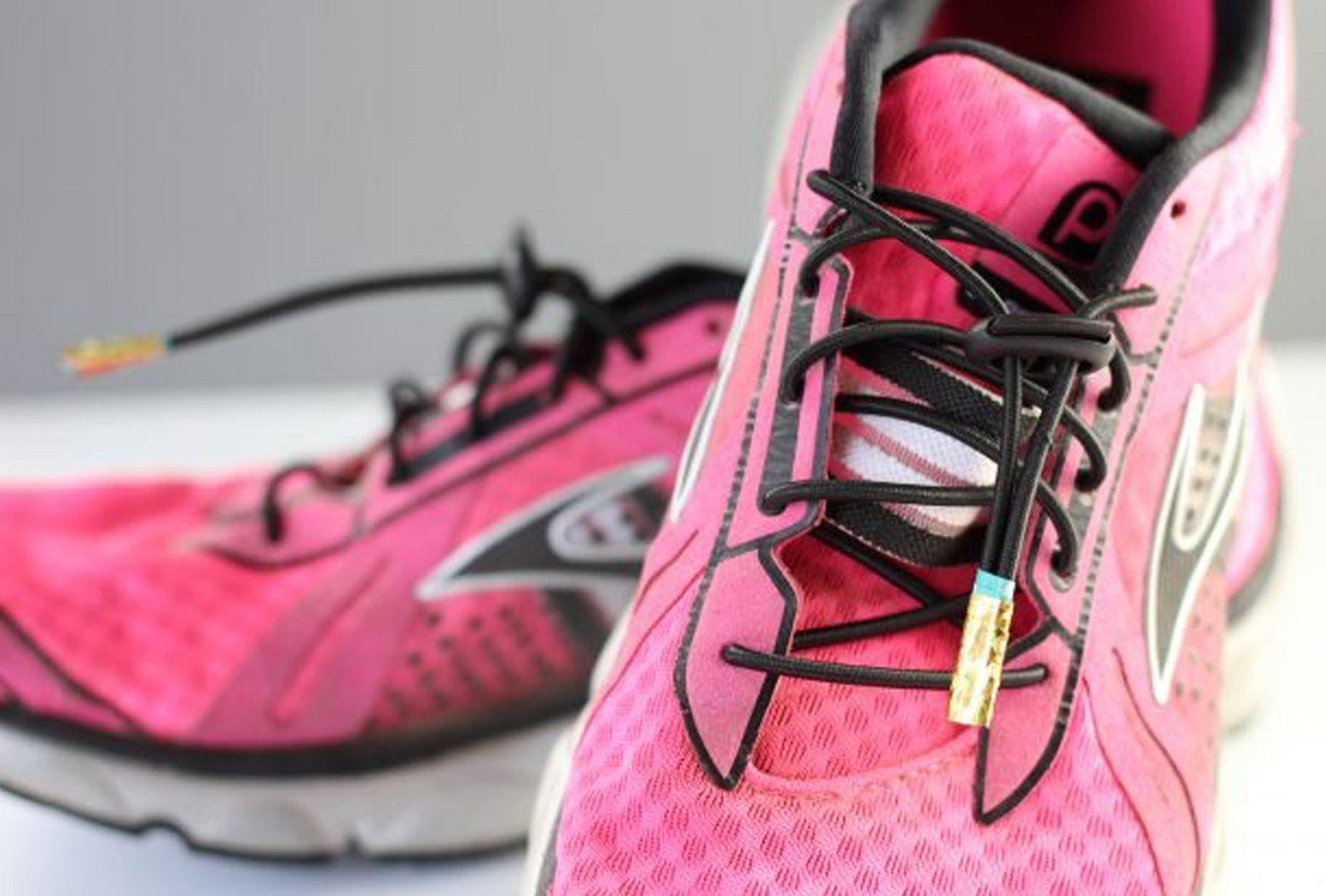 pink running shoes with gold lace tips