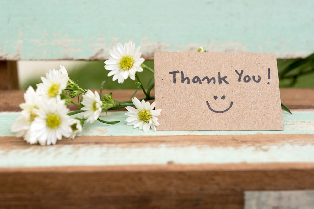 Thank you note with smile face and flower cluster on wooden chair