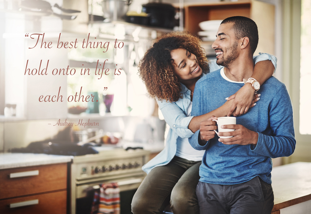 a couple, in love, in their kitchen with a cute love quote