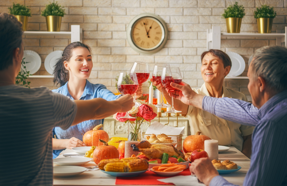 Family celebrates thanksgiving with a toast and Thanksgiving traditions