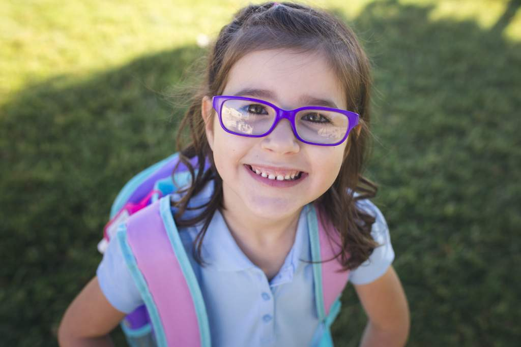 A girl wearing a uniform and a backpack is ready for her first day of school and school picture day.