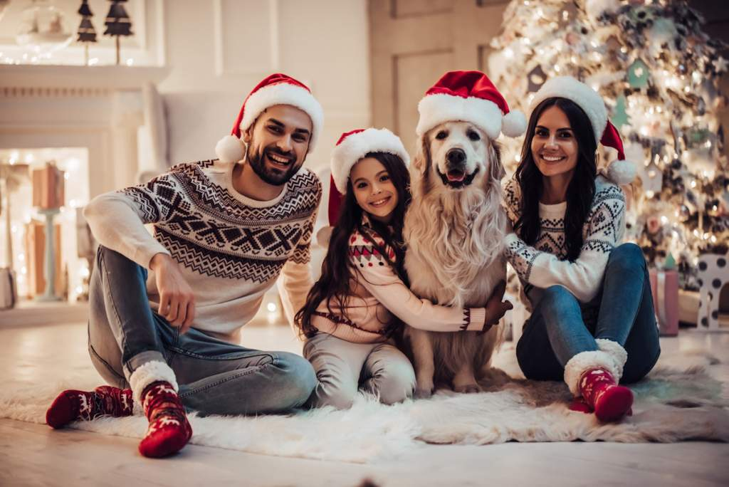 Merry Christmas and Happy New Year! Happy family with dog labrador retriever are waiting for the New Year in Santa Claus hats while sitting near beautiful Christmas tree at home for a family picture.