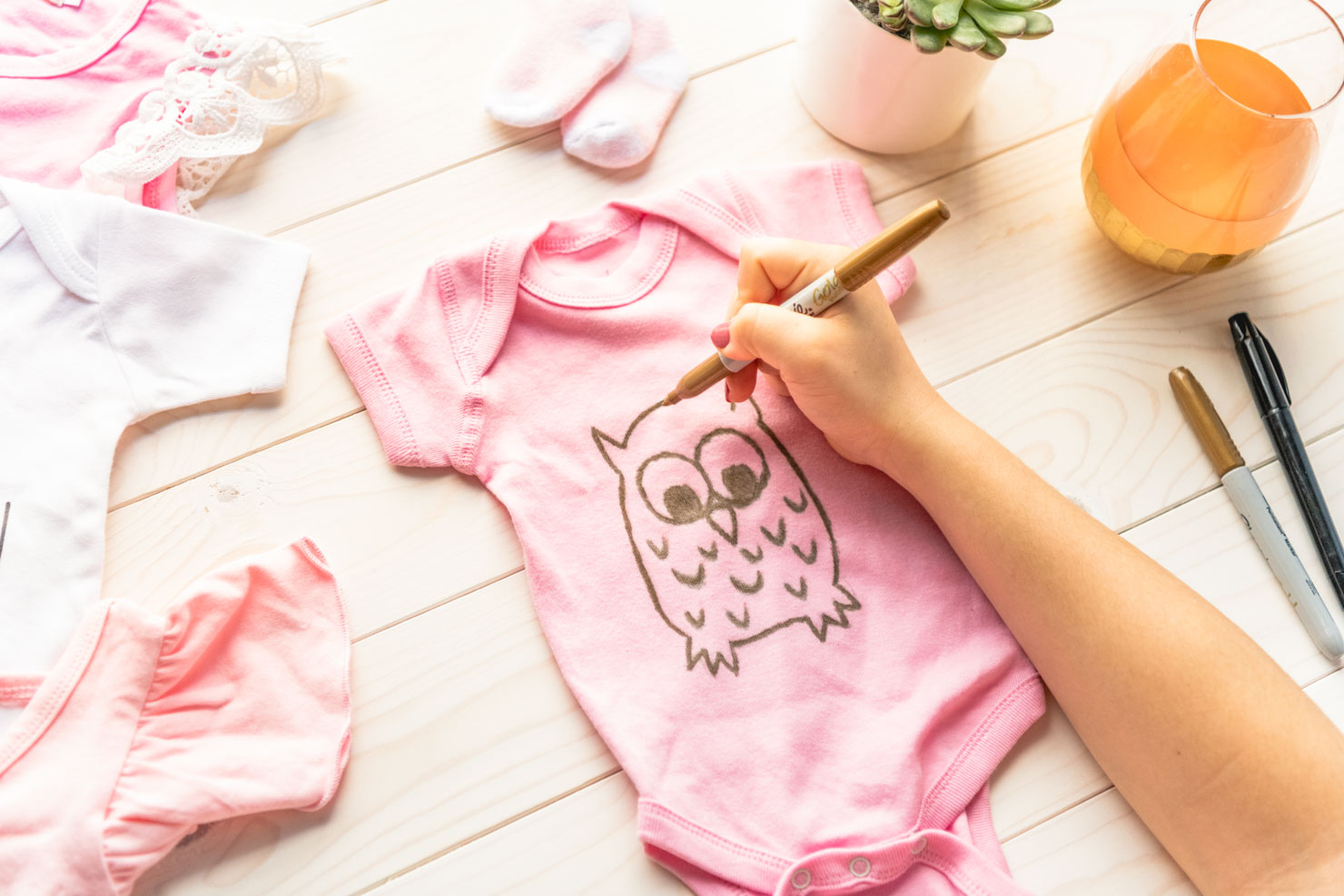 someone painting a baby onesie with a gold marker