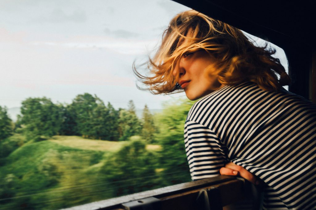 woman looking at the view from train window