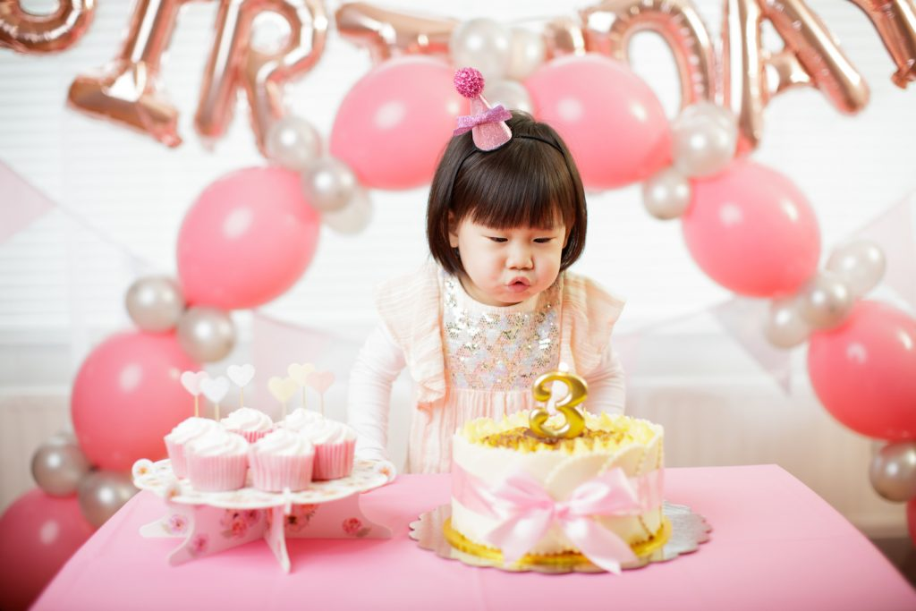 toddler girl celebrating her third birthday at a party hall