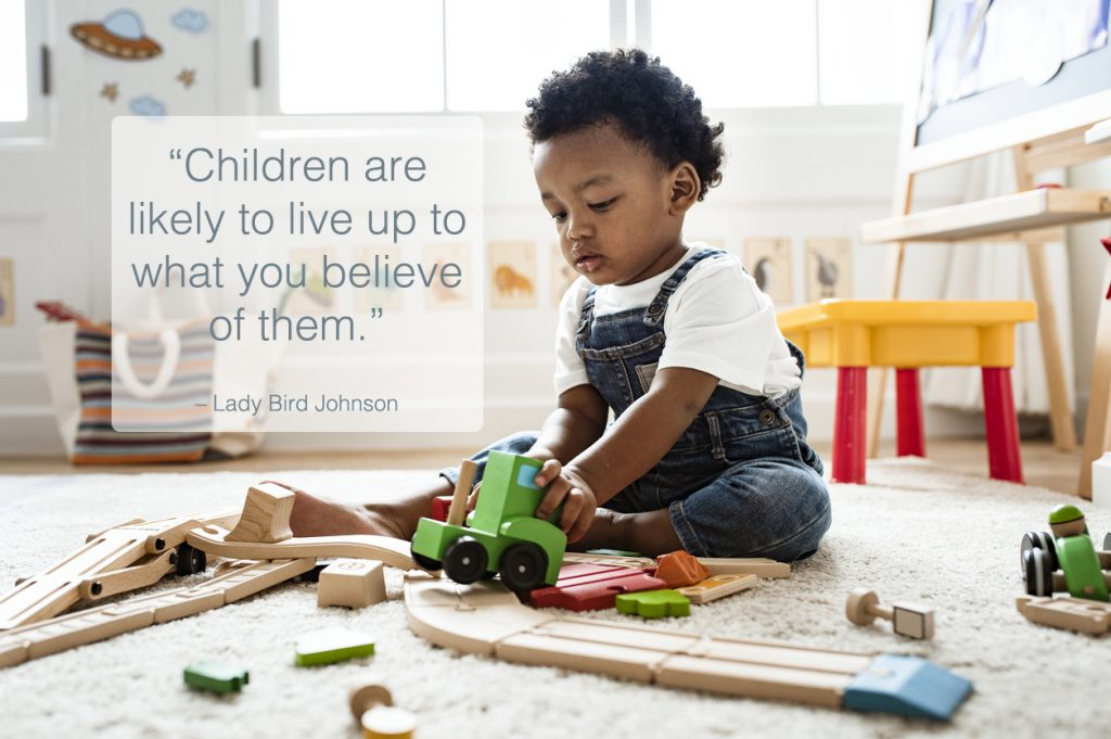 Cute little boy playing with a railroad train toy with children quotes overlay