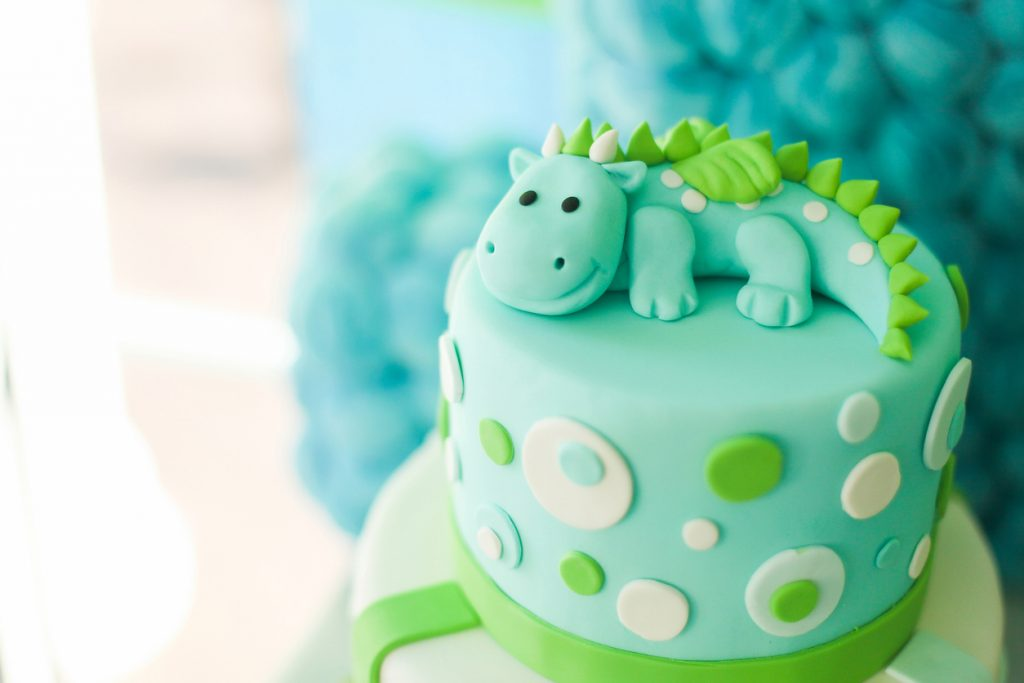 Blue and green first year birthday cake with cute dinosaur.