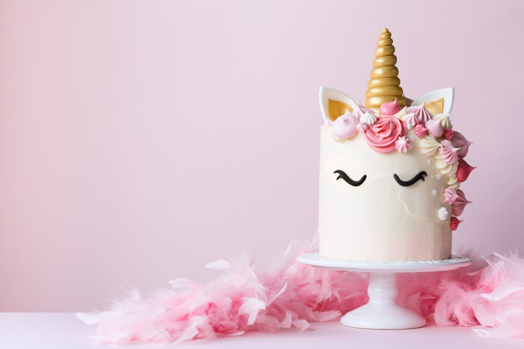 Unicorn cake with pink frosting for cute unicorn birthday party ideas