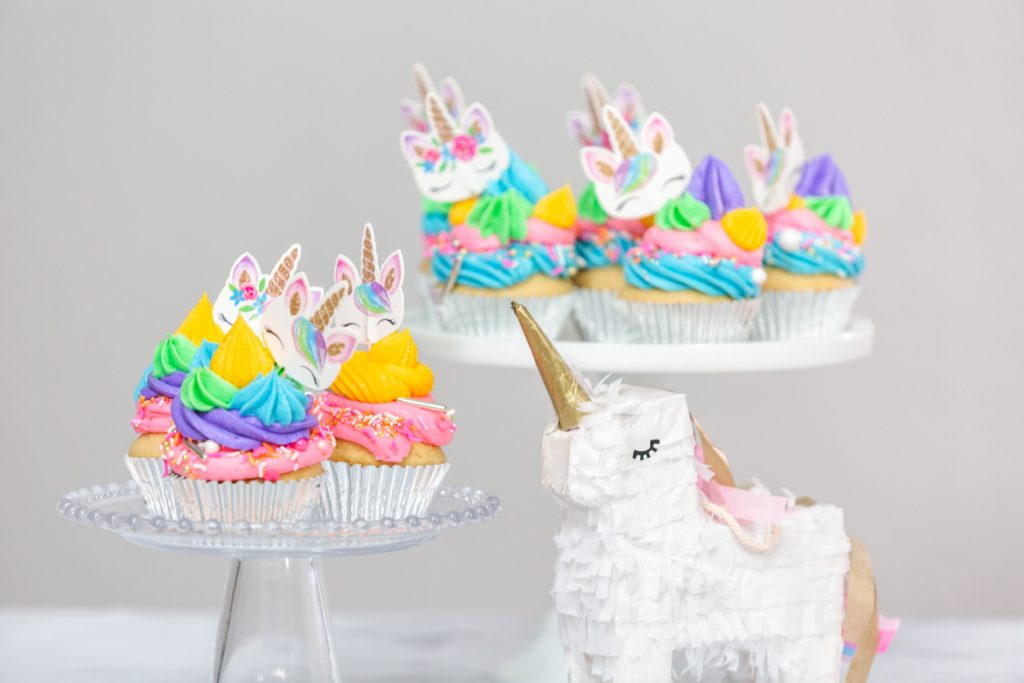 Unicorn piñata and cupcakes with multicolor buttercream icing on cake stands.