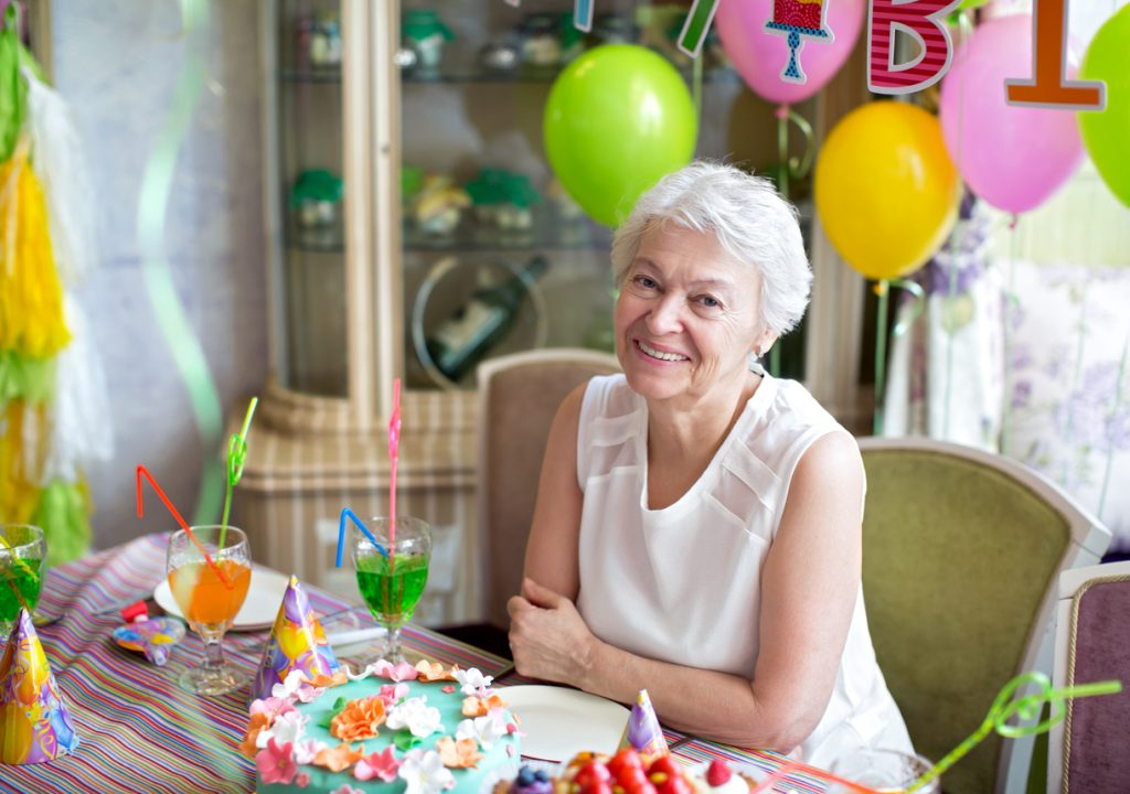 Smiling elderly woman at an 80th birthday party with tropical decorations.